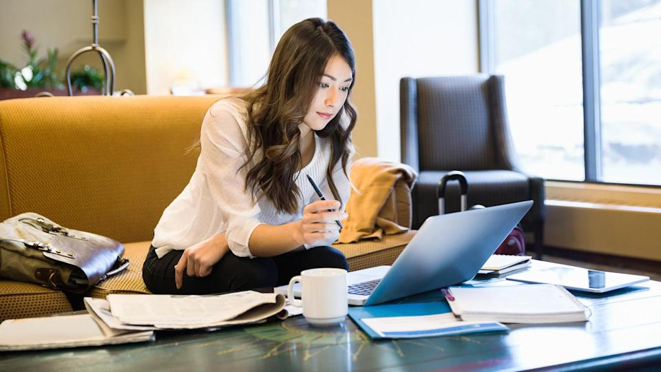 Businesswoman working at laptop in lobby.
