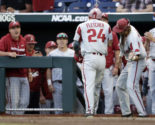Arkansas' Dominic Fletcher (24) is greeted at the dugout after his solo home run against Florida in the fifth inning of an NCAA College World Series baseball game in Omaha, Neb., Friday, June 22, 2018. (AP Photo/Nati Harnik)