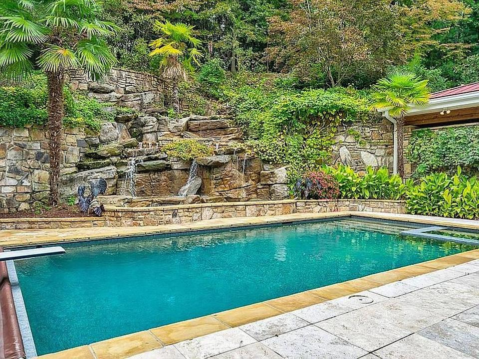 The home features an outdoor kitchen, cabana, heated in-ground pool and a two-story waterfall.