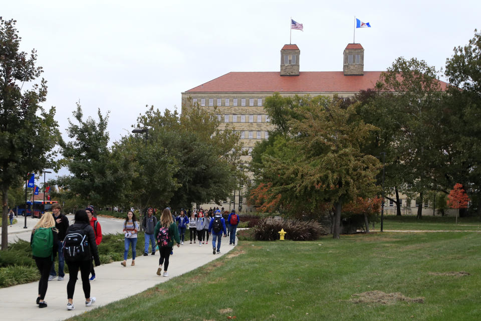 FILE - In this Oct. 24, 2019, file photo students walks in front of Fraser Hall on the University of Kansas campus in Lawrence, Kan. Americans collectively owe nearly $1.5 trillion in student loans, more than twice the total a decade ago. It's a burden that weighs on millions of adults, shaping their life choices and often stunting their financial growth. (AP Photo/Orlin Wagner, File)