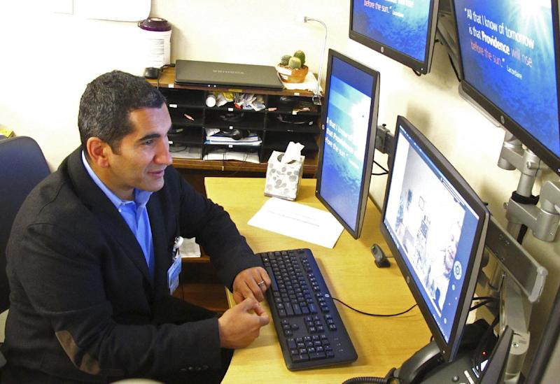 In this photo taken Sept. 13, 2016, critical care doctor Shadi Battah in Anchorage, Alaska, converses with clinicians at the Iliuliuk Family and Health Services on Unalaska Island during a demonstration of a new telemedicine partnership with Providence Alaska Medical Center. Beginning Thursday, Sept. 22, the Anchorage hospital will virtually beam critical care doctors 800 miles away to the emergency room of the clinic to assist staffers there during medical emergencies, thanks to a satellite link instead of the usual fiber optics. (AP Photo/Rachel D'Oro)