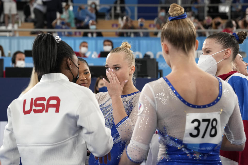 Simone Biles, of the United States, congratulates gymnasts from the Russian Olympic Committee's Liliia Akhaimova, back to camera, Vladislava Urazova, right, and Angelina Melnikova after they won the gold medal at the 2020 Summer Olympics, Tuesday, July 27, 2021, in Tokyo. (AP Photo/Ashley Landis)