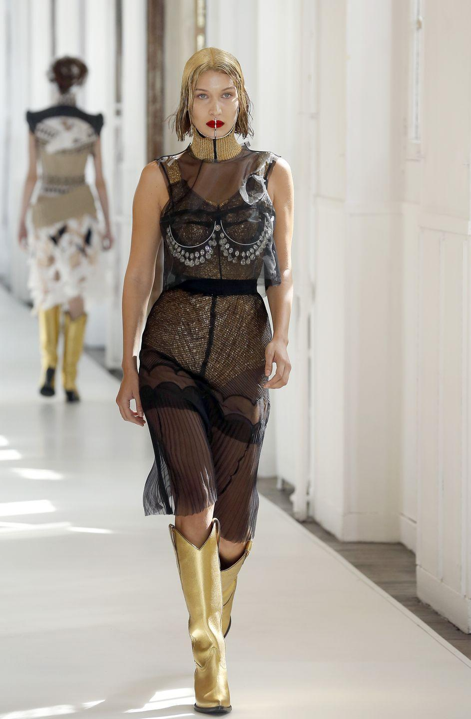 <p>Bella stomped down the runway wearing a black sheer dress, gold boots and spray-painted gold glitter hair for the Maison Margiela show, 5 July 2017</p>
