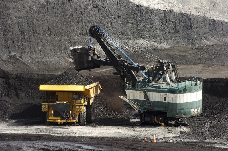 FILE - In this April 4, 2013, file photo, a mechanized shovel loads a haul truck that can carry up to 250 tons of coal at the Spring Creek coal mine near Decker, Mont. Federal officials say the Trump administration's decision to lift a moratorium on coal sales from public lands could hasten the release of more than 5 billion tons of greenhouse gasses. The report comes after a court ruled last month that the administration failed to consider the environmental effects of its resumption in 2017 of coal sales. A moratorium had been imposed under President Barack Obama over worries about climate change. (AP Photo/Matthew Brown, File)