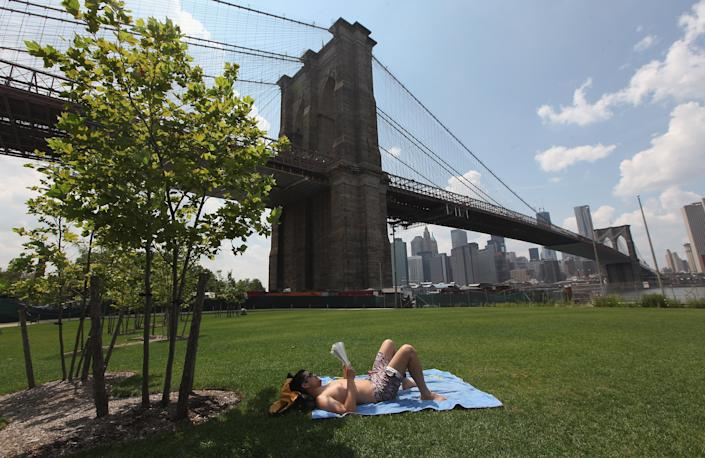 Isaac O'neill reads a newspaper in Brooklyn Bridge Park on July 16, 2012 in the Brooklyn borough of New York City. A heat advisory was issued in the city again today as high temperatures were expected in the 90?s the next three days. (Photo by Mario Tama/Getty Images)