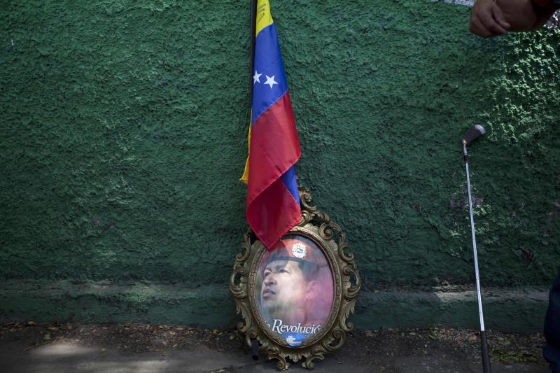 FILE - In this Oct. 3, 2012 file photo, a framed image of Venezuela's President Hugo Chavez is propped up against a wall, under a Venezuelan flag next to a golf club at a campaign rally in Maracay, Venezuela. After four election wins, Chavez is on track to completing at least 20 years in power. (AP Photo/Rodrigo Abd, File)