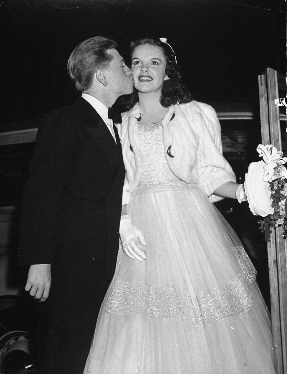 """Rooney kisses Garland as they arrive at the """"Babes in Arms"""" movie premiere in 1939."""