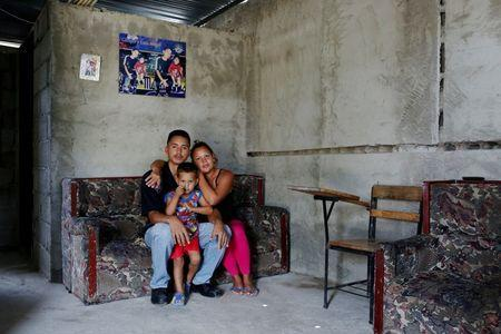 Oleydy Canizalez, 29, poses for a picture with her husband Julio Espinoza, 28, and her son Luis, 3, before her sterilization surgery, at their home in Charallave, Venezuela July 7, 2016. REUTERS/Carlos Garcia Rawlins