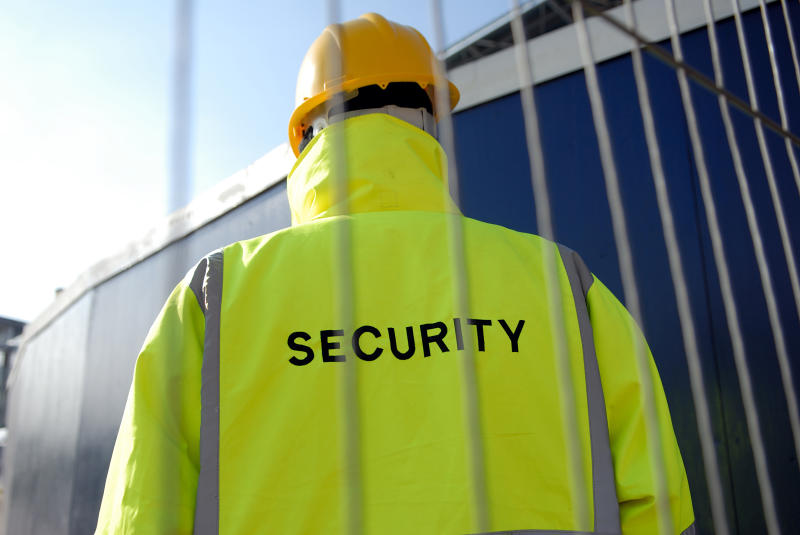 Low view of a security man behind a wire fence wearing a hardhat on a construction site.