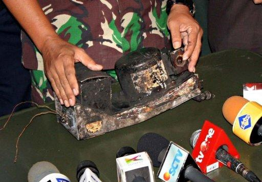 An Indonesian military officer displays the charred black box of the Russian Sukhoi Superjet 100