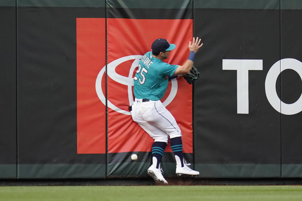 Seattle Mariners left fielder Dylan Moore collides with the wall after chasing a deep fly that dropped in for a single by Kansas City Royals' Salvador Perez during the first inning of a baseball game Friday, Aug. 27, 2021, in Seattle. (AP Photo/Elaine Thompson)
