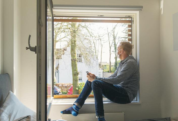 """<span class=""""caption"""">Open windows are the simplest way to increase air flow in a room.</span> <span class=""""attribution""""><a class=""""link rapid-noclick-resp"""" href=""""https://www.gettyimages.com/detail/photo/man-with-mask-looking-out-of-window-royalty-free-image/1215148858?adppopup=true"""" rel=""""nofollow noopener"""" target=""""_blank"""" data-ylk=""""slk:Justin Paget / Digital Vision via Getty Images""""> Justin Paget / Digital Vision via Getty Images</a></span>"""