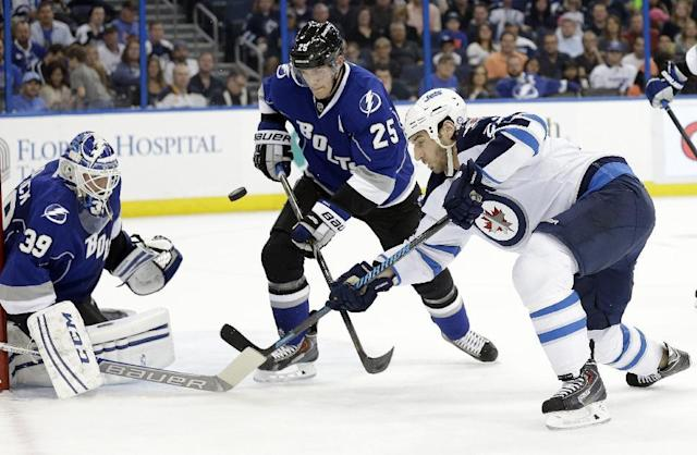 Winnipeg Jets right wing Chris Thorburn (22) shoots on Tampa Bay Lightning goalie Anders Lindback (39), of Sweden, as Lightning defenseman Matt Carle (25) moves in during the first period of an NHL hockey game on Saturday, Dec. 7, 2013, in Tampa, Fla. (AP Photo/Chris O'Meara)