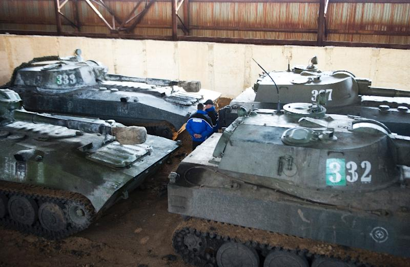 An International monitor of the Organization for Security and Co-operation in Europe stands amidst self-propelled guns of the self-proclaimed People Republic of Donetsk in a hangar in Snizhne, Ukraine, on March 7, 2015 (AFP Photo/John MacDougall)