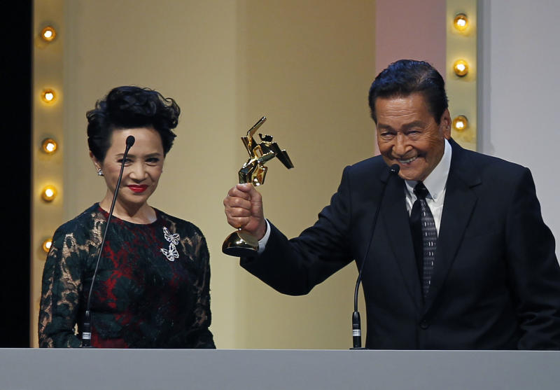 """Actor Eddie Garcia of the Philippines raises his trophy after winning the People's Choice Favourite Actor award for his role in the film """" Bwakaw """", at the Asian Film Awards in Hong Kong Monday, March 18, 2013. At left is the Hong Kong actress Deanie Ip. (AP Photo/Vincent Yu)"""