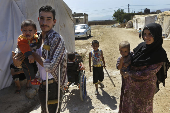 In this Wednesday, Sept. 11, 2013 file photo, Syrian refugee, Mohammed Ahmed, 20, right, who fled his home with his family from Baba Amro, Homs province, carries his son at a temporary refugee camp, in the eastern Lebanese Town of Al-Faour, Bekaa Valley near the border with Syria, Lebanon. With some 1 million Syrian refugees in Lebanon, or nearly 25 percent of the tiny Arab country's population, the guests from Lebanon's eastern neighbor are facing different kinds of racist behaviors by Lebanese. (AP Photo/Hussein Malla, File)