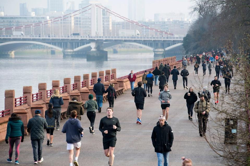 <p>People walk and run through Battersea Park during England's third national lockdown</p> (PA)