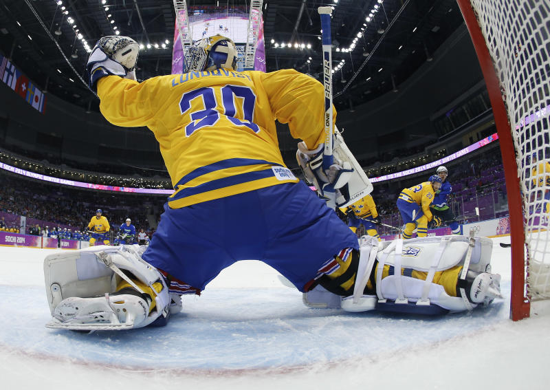 Sweden goaltender Henrik Lundqvist blocks a shot by Slovenia in the first period of a men's ice hockey game at the 2014 Winter Olympics, Wednesday, Feb. 19, 2014, in Sochi, Russia. (AP Photo/Julio Cortez, Pool)