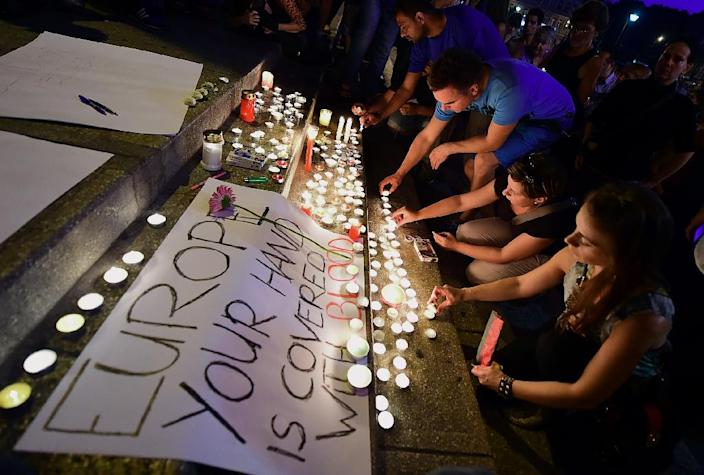 """People light candles next to a banner reading """"Europe, your hand is covered with blood"""" in front of the Eastern railway station in Budapest on August 28, 2015 (AFP Photo/Attila Kisbenedek)"""