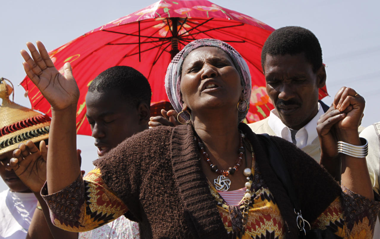 A woman from a group of churchgoers wails at the site, Sunday Aug. 19, 2012 at the Lonmin platinum mine, background, near Rustenburg, South Africa, during a memorial service for 34 dead striking miners who were shot and killed bt police last Thursday. Miners must return to work Monday or face being fired from the mine where rivalry between unions has exploded into violence. (AP Photo/Denis Farrell)