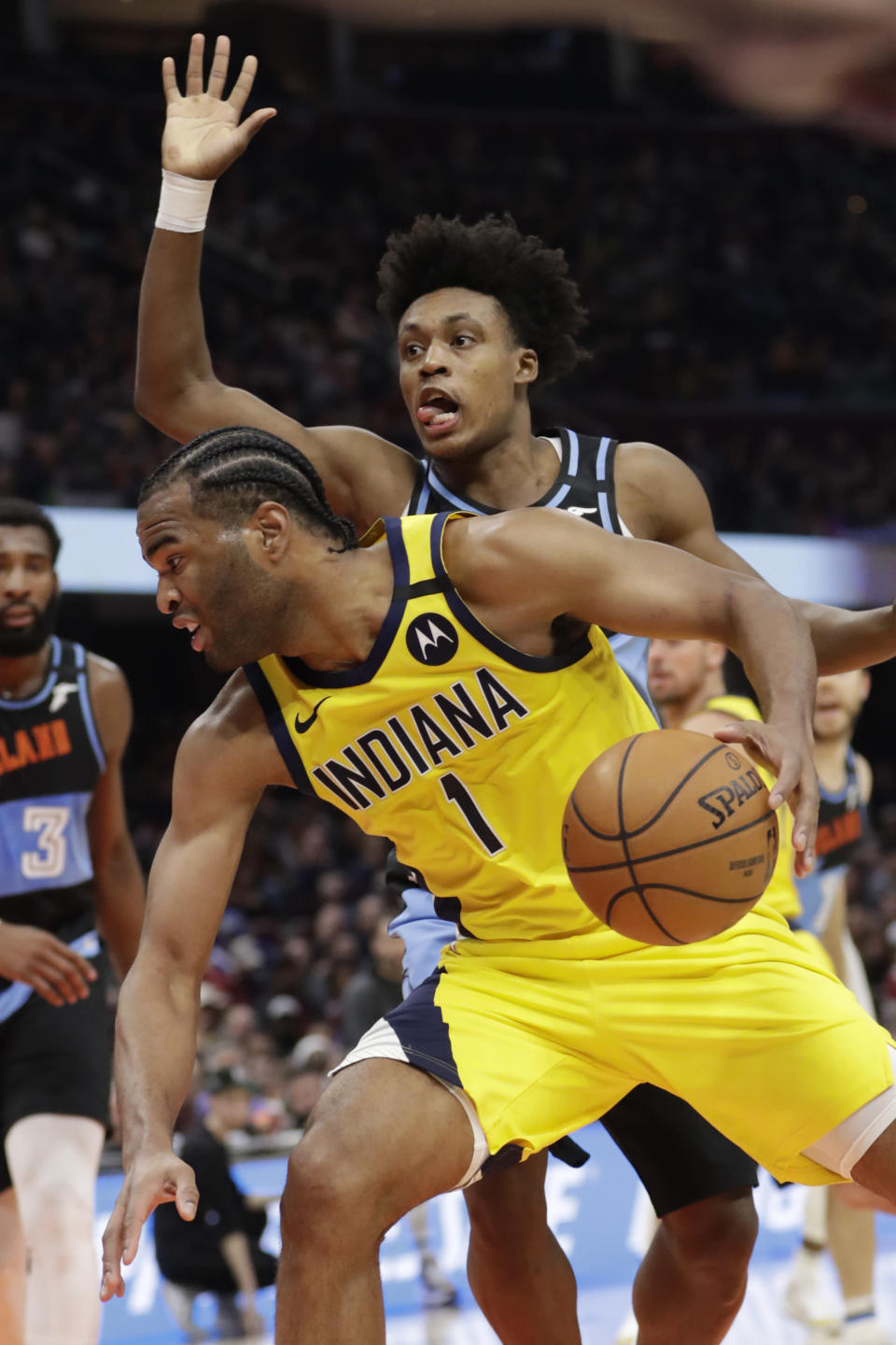 Indiana Pacers' T.J. Warren (1) drives past Cleveland Cavaliers' Collin Sexton (2) in the second half of an NBA basketball game, Saturday, Feb. 29, 2020, in Cleveland. Indiana won 113-104. (AP Photo/Tony Dejak)