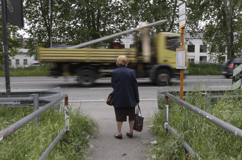 An elderly woman waits for a bus in Milan, Italy, Wednesday, May 15, 2013. The recession across the economy of the 17 European Union countries that use the euro extended into its sixth quarter longer than the calamitous slump that hit the region in the financial crisis of 2008-9. (AP Photo/Luca Bruno)