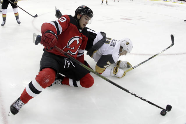 New Jersey Devils center Nico Hischier (13), of Switzerland, and Vegas Golden Knights center William Karlsson (71), of Sweden, fall to the ice while competing for the puck during the second period of an NHL hockey game, Friday, Dec. 14, 2018, in Newark. (AP Photo/Julio Cortez)