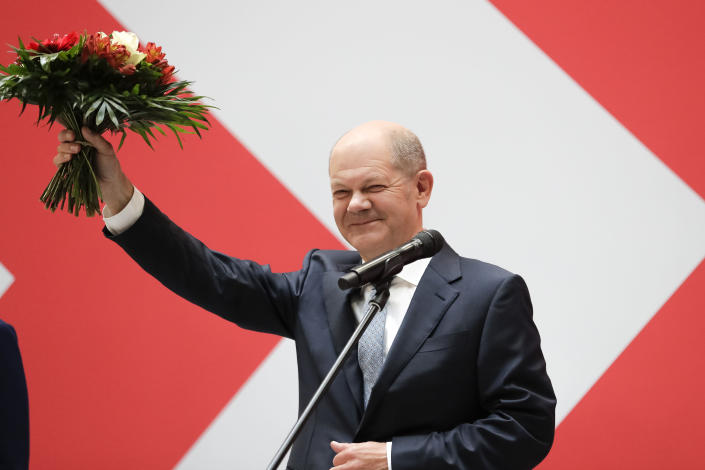Olaf Scholz, top candidate for chancellor of the Social Democratic Party (SPD), holds a bunch of flowers after a press statement at the party's headquarter in Berlin, Germany, Monday, Sept. 27, 2021. The center-left Social Democrats have won the biggest share of the vote in Germany's national election. They narrowly beat outgoing Chancellor Angela Merkel's center-right Union bloc in a closely fought race that will determine who succeeds the long-time leader at the helm of Europe's biggest economy. (AP Photo/Lisa Leunter)
