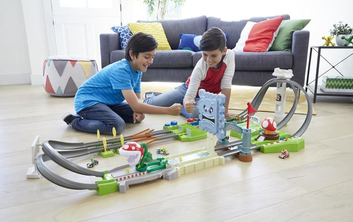 Two boys playing with a racing track.