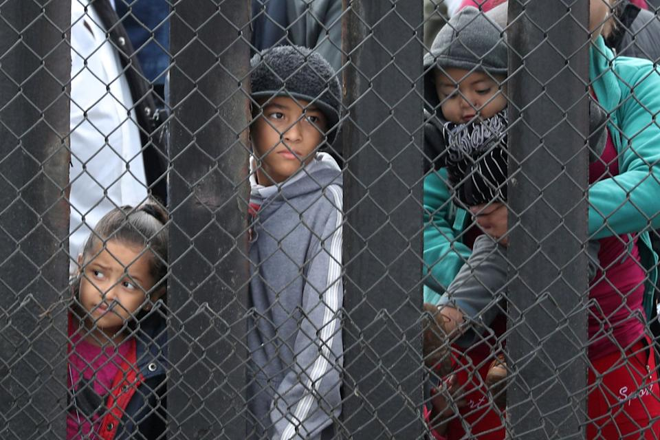 Children look through the U.S.-Mexico border wall at Border Field State Park.