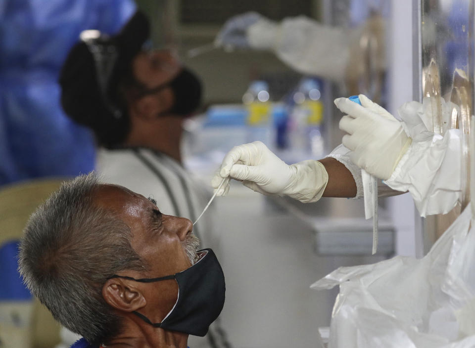 Residents react as they undergo a free COVID-19 swab test in a low income area of Manila, Philippines, Tuesday, Oct. 6, 2020. The city government is providing free swab tests to tricycle and passenger Jeepney drivers in the area in hopes of curbing the spread of the coronavirus. (AP Photo/Aaron Favila)