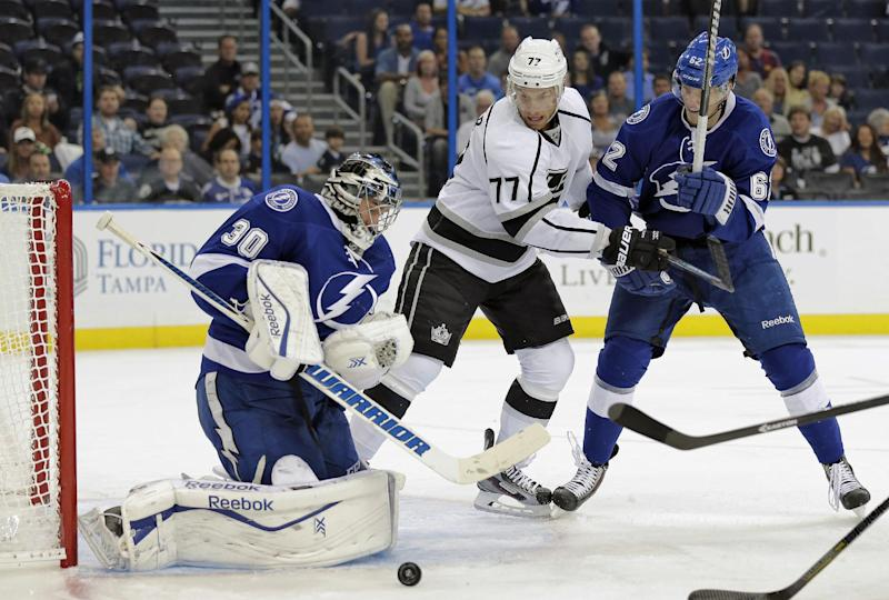 Tampa Bay Lightning goalie Ben Bishop (30) makes a save on a deflection by Los Angeles Kings center Jeff Carter (77) as Lightning defenseman Andrej Sustr, of the Czech Republic, defends during the first period of an NHL hockey game Tuesday, Oct. 15, 2013, in Tampa, Fla. (AP Photo/Chris O'Meara)