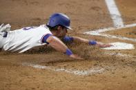 Texas Rangers' DJ Peters slides into home, scoring from first on a single by Curtis Terry during the second inning of the team's baseball game against the Los Angeles Angels in Arlington, Texas, Tuesday, Aug. 3, 2021. (AP Photo/Tony Gutierrez)