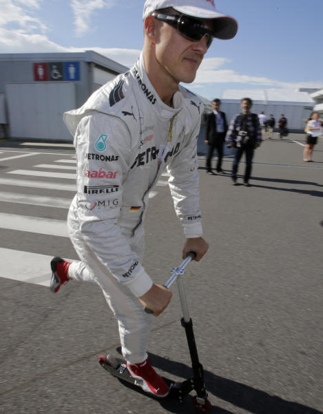 Mercedes driver Michael Schumacher of Germany rides a scooter through the F1 paddock at the Suzuka Circuit venue for the Japanese Formula One Grand Prix in Suzuka, Japan, Thursday, Oct. 4, 2012. (AP Photo/Shizuo Kambayashi)