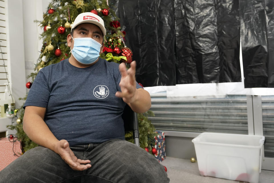 Gustavo Ajche, 38, who has three jobs, gestures after watching Joe Biden's presidential inauguration on TV with other immigrants at the offices of the Workers Justice Center, Wednesday, Jan. 20, 2021, in the Sunset Park neighborhood in New York. Atche has been in the United States since 2004. His wife is in the United States but his children are back in Guatemala while he and his wife pay for their college education there. Atche works construction, delivers food for food delivery applications, and works helping his community at a food pantry in Brooklyn. (AP Photo/Kathy Willens)