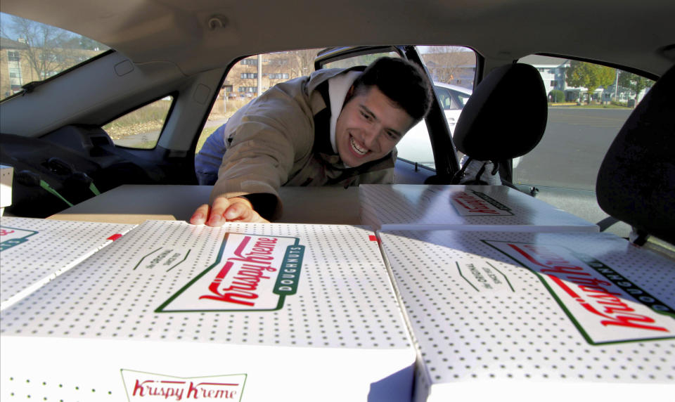 In this Saturday, Oct. 26, 2019 photo, Jayson Gonzalez reaches into his car for another box of Krispy Kreme doughnuts for customers in Little Canada, Minn, who ordered online. Gonzalez, a Minnesota college student, says Krispy Kreme has told him to stop making doughnut runs to Iowa. Gonzalez told the Pioneer Press he was told his sales created a liability for the North Carolina-based company. (Deanna Weniger/Pioneer Press via AP)
