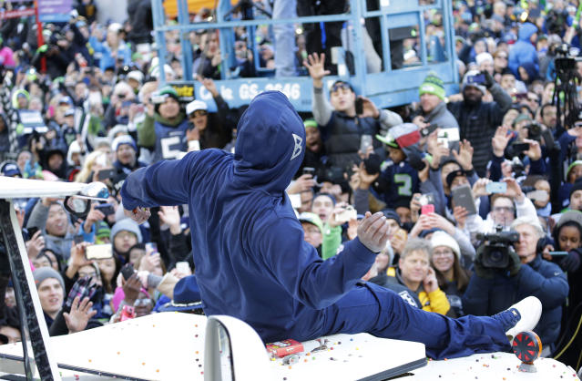 Seattle Seahawks' running back Marshawn Lynch throws pieces of Skittles candy while riding on the hood of a vehicle during the Super Bowl champions parade on Wednesday, Feb. 5, 2014, in Seattle. The Seahawks beat the Denver Broncos 43-8 in NFL football's Super Bowl XLVIII on Sunday. (AP Photo/Ted S. Warren)