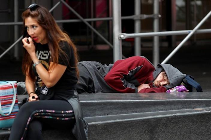 A man lays on a bench at Times Square in New York City