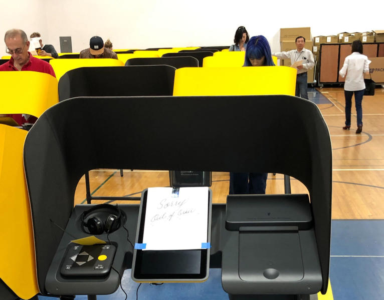"""A sign reads """"Sorry, Out of Order,"""" on a voting station as people cast the ballots Tuesday, March 3, 2020, at the Silverlake Independent Jewish Community Center in Los Angeles. Poll workers said that computer network issues slowed both the voter check-in process and made some machines unusable. About one-third of the approximately 40 machines were being used. The resulting line meant voting took about an hour. (AP Photo/Justin Pritchard)"""