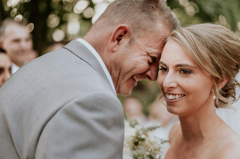 A close-up of the bride and groom's smiling faces, their foreheads touching. The groom is in profile, with the bride angled toward the camera. (James Day Photography)