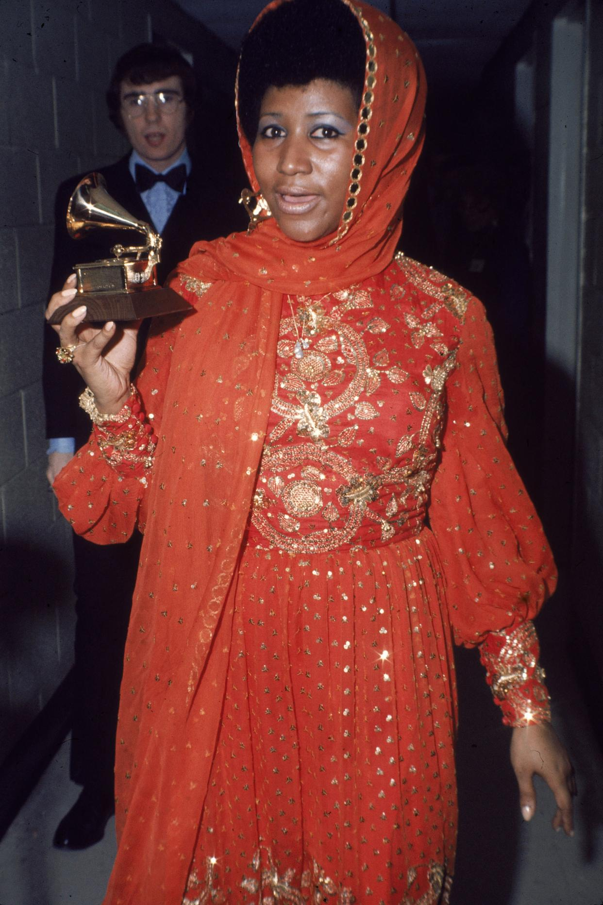 Standing backstage wearing a gold embroidered gown and holding a Grammy Award, circa 1970.
