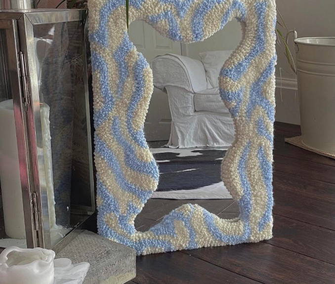 """This wouldn't be a story about tufting if we didn't include an example of the <a href=""""https://refinery29.com/en-gb/best-wall-mirrors-decorative"""" rel=""""nofollow noopener"""" target=""""_blank"""" data-ylk=""""slk:fun mirrors"""" class=""""link rapid-noclick-resp"""">fun mirrors</a> we've been seeing everywhere. Perfect for embodying that <a href=""""https://refinery29.com/en-gb/fake-decor-instagram-homeware-trend"""" rel=""""nofollow noopener"""" target=""""_blank"""" data-ylk=""""slk:playful, early '00s style"""" class=""""link rapid-noclick-resp"""">playful, early '00s style</a>.<br><br><strong>Angel Delights</strong> Rug Mirror, $, available at <a href=""""https://www.etsy.com/uk/listing/989808987/rug-mirror?"""" rel=""""nofollow noopener"""" target=""""_blank"""" data-ylk=""""slk:Etsy"""" class=""""link rapid-noclick-resp"""">Etsy</a>"""