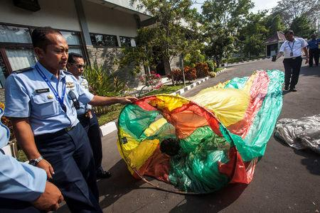 Officers show an unmanned hot air balloon, used in traditional festivities for celebrating Eid al-Fitr, during a press conference at  AirNav Indonesia, in Yogyakarta