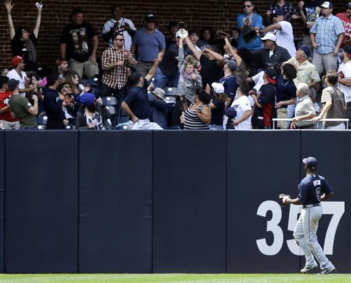 Atlanta Braves left fielder Justin Upton watches as fans battle for a home run ball hit by San Diego Padres' Chris Denorfia in the fifth inning of a baseball game on Wednesday, June 12, 2013, in San Diego. (AP Photo/ Lenny Ignelzi)