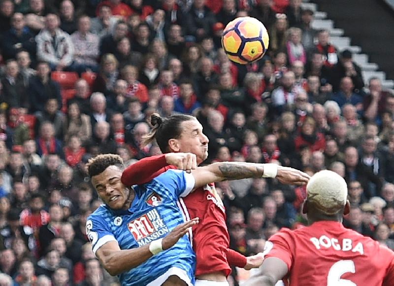 Manchester United's striker Zlatan Ibrahimovic (C) clashes in the air with Bournemouth's defender Tyrone Mings (L) during the English Premier League football match between Manchester United and Bournemouth at Old Trafford on March 4, 2017