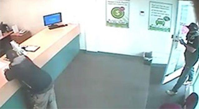 A thief jumps the counter and demands cash from a money lending store, then helps himself to money in the safe. Pictures: Victoria Police