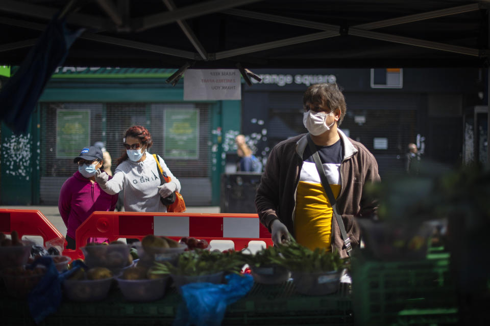 Shoppers wearing protective face masks at a fruit and vegetable market stall in East Ham, east London, as the UK continues in lockdown to help curb the spread of the coronavirus. (Photo by Victoria Jones/PA Images via Getty Images)