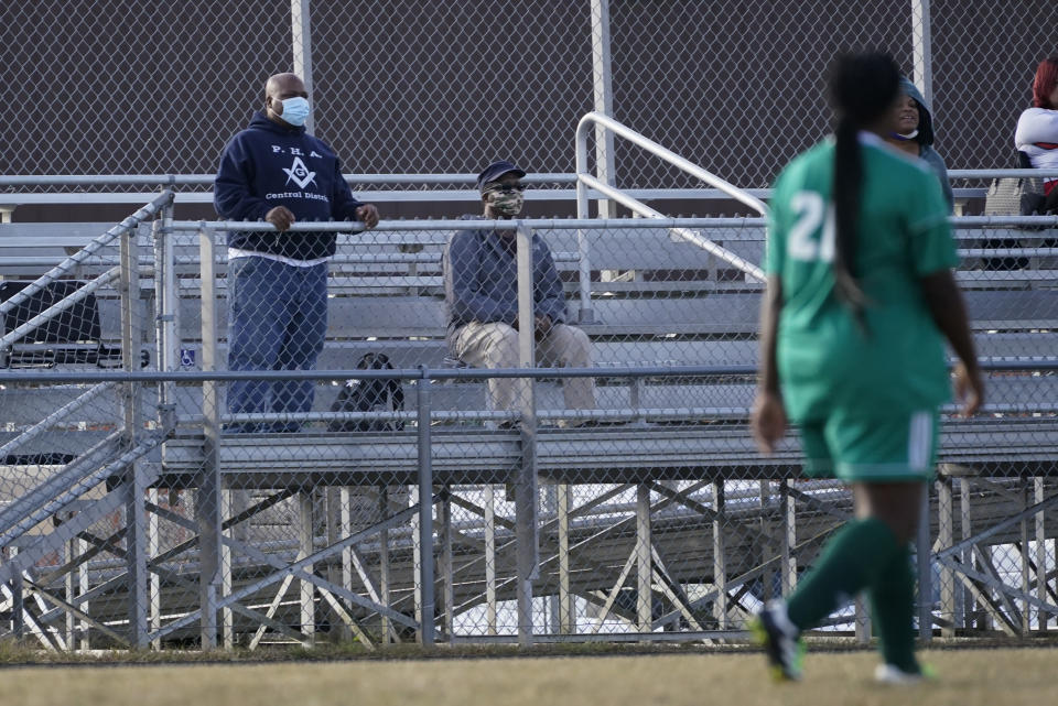 Larry Brown, left, and his father, John Brown, watch Larry's daughter, Justys Glenn, right, play in a soccer game, Wednesday, Sept. 30, 2020, in Indianapolis. He didn't die after contracting COVID-19, but he's coming to terms with the fact that his life might never be the same. (AP Photo/Darron Cummings)