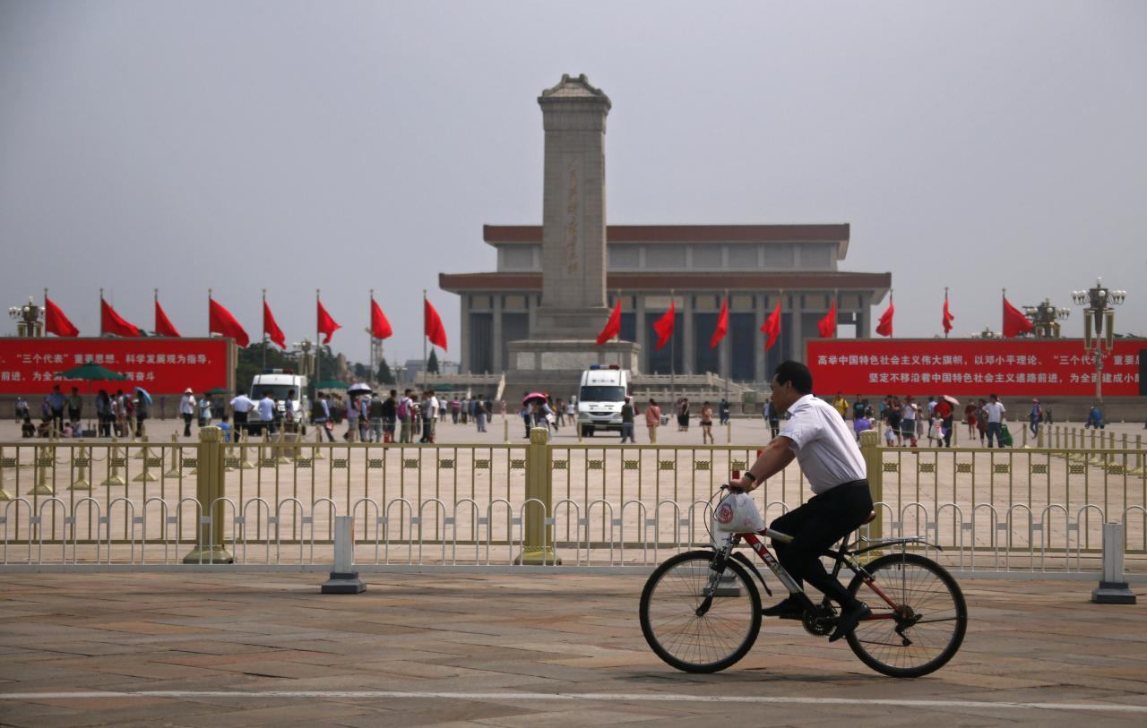 """REFILE - CORRECTING GRAMMAR  A man rides past the Monument to the People's Heroes at Tiananmen Square in Beijing June 4, 2014. China deployed its vast security apparatus on Wednesday to snuff out commemoration of the suppression of pro-democracy protests around Tiananmen Square 25 years ago, flooding the streets with police as censors scrubbed the Internet clean of any mention of the crackdown. The Chinese characters on the screen (R) read, """"Holding the great banner of socialism with Chinese characteristics, follow the guidance of the Deng Xiaoping Theory and the important thought of Three Represents, unswervingly progressing along the path of socialism with Chinese characteristics."""" REUTERS/Petar Kujundzic (CHINA - Tags: MILITARY POLITICS ANNIVERSARY SOCIETY)"""