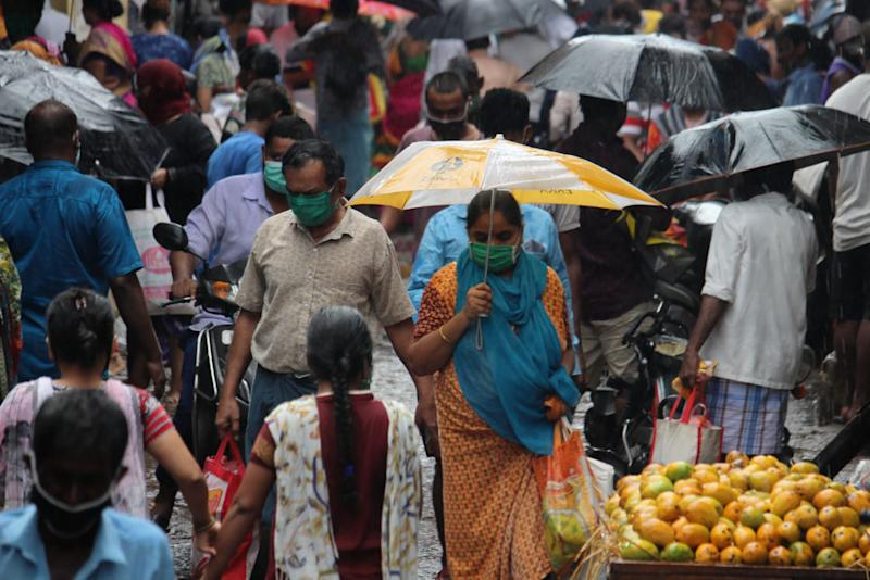 Shoppers crowd a street during heavy rains in Mumbai on June 3. Source: Getty